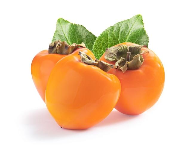 Trzy dojrzałe soczyste słodkie persimmons z zielonymi liśćmi na białym tle