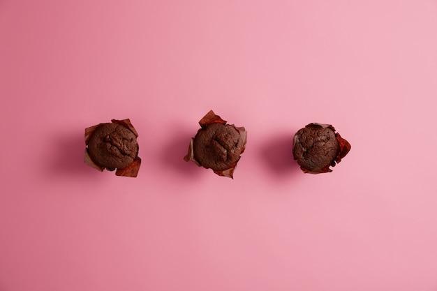 Trzy domowe babeczki czekoladowe do jedzenia z herbatą. smaczne babeczki kupione w sklepie piekarniczym. ciasta na śniadanie lub rodzinny piknik. koncepcja piekarni i wyrobów cukierniczych. pyszny słodki deser.