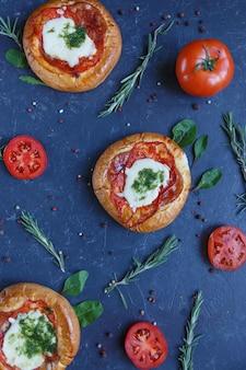 Trzy domowe mini pizza z pomidorami, serem i boczkiem, urazy i przyprawy.