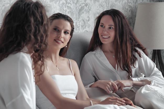 Trzy dorosłe kobiety w stylowych, swobodnych białych ubraniach spędzają czas w łóżku, słodko rozmawiają, opowiadają historie i śmieją się. dorośli przyjaciele spotykali się i spędzali wolny czas w pokoju hotelowym. koncepcja kobiecej przyjaźni