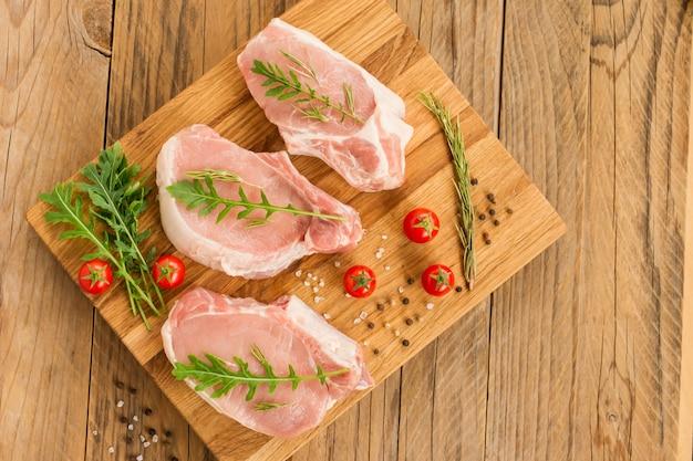 Trzy doskonałe kawałki świeżej wieprzowiny na krojonej desce kuchennej z liśćmi rukoli i pomidorem. widok z góry.