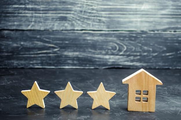 Trzy drewniane gwiazdki i dom. trzygwiazdkowy hotel lub restauracja. recenzja krytyka.