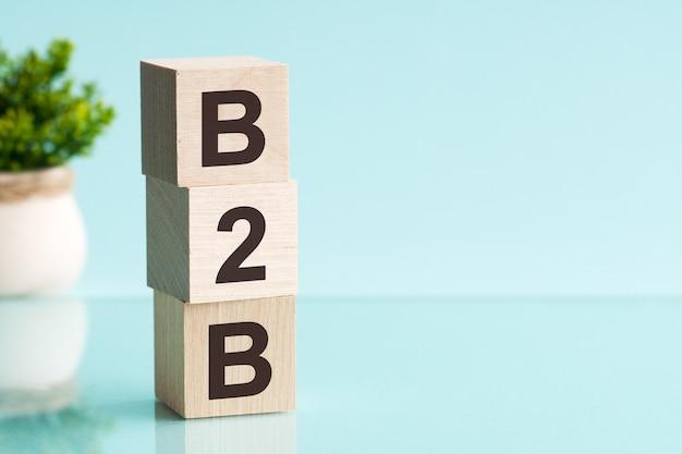 Trzy drewniane kostki z literami - b2b - skrót od business to business, na niebieskim stole
