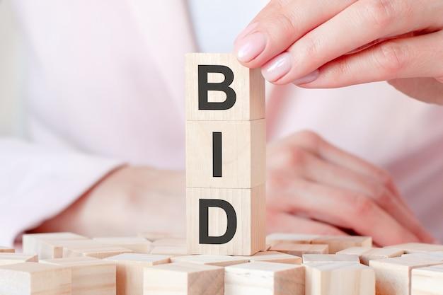 Trzy drewniane kostki z literami bid, na tle kobiecych dłoni w różowych ubraniach. koncepcja biznesowa i ekonomiczna.