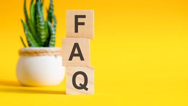 Trzy drewniane kostki z literami - faq na żółtym stole, po prawej miejsce na tekst. koncepcje widoku z przodu, kwiat w tle. faq - skrót od najczęściej zadawanych pytań