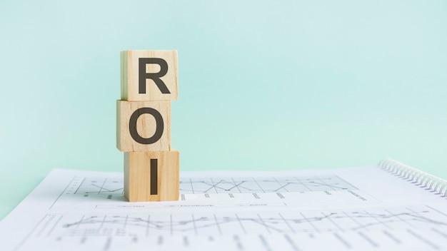 Trzy drewniane kostki z literami roi - czyli zwrot z inwestycji, na białym stole.