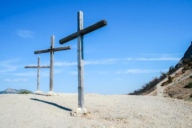 Trzy drewniane krzyże w górach na tle nieba