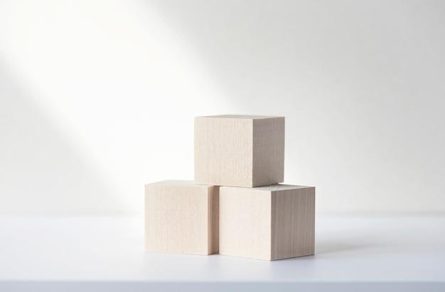 Trzy drewniane kwadratowe klocki lub kostki na białym biurku. makieta, miejsce na tekst. koncepcyjny obraz biznesowy