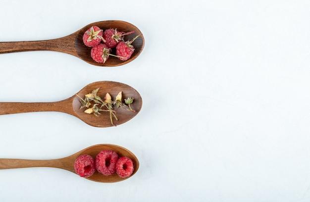 Trzy drewniane łyżki czerwonych malin i suchych liści na kamiennej powierzchni