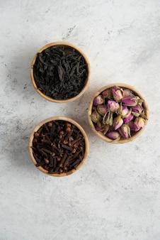 Trzy drewniane miseczki z suszonymi różami, goździkami i sypką herbatą.
