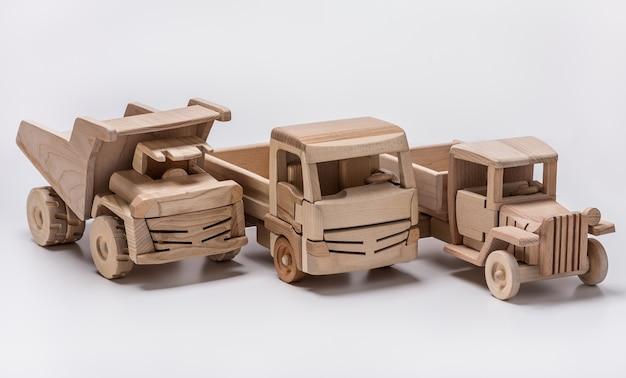 Trzy drewniane samochody pamiątkowe. ciężarówki i wywrotki.