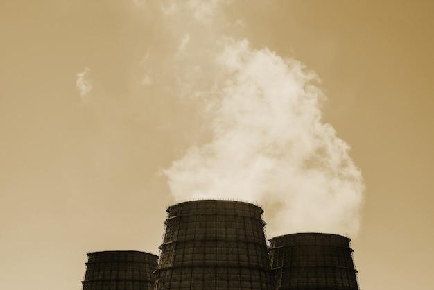 Trzy duża wieża zbliżenia chpp. para z szerokiej rury chp na niebie. przemysłowe tło tpp w odcieniach sepii z miejsca kopiowania. ogromne rury elektrowni cieplnej wytwarzają parę dla energii elektrycznej.
