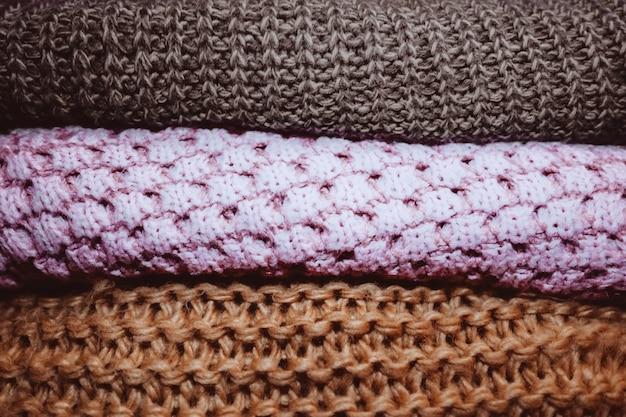 Trzy dzianinowe przytulne swetry leżące w rzędzie koncepcja jesienno-zimowych ubrań ciepły materiał