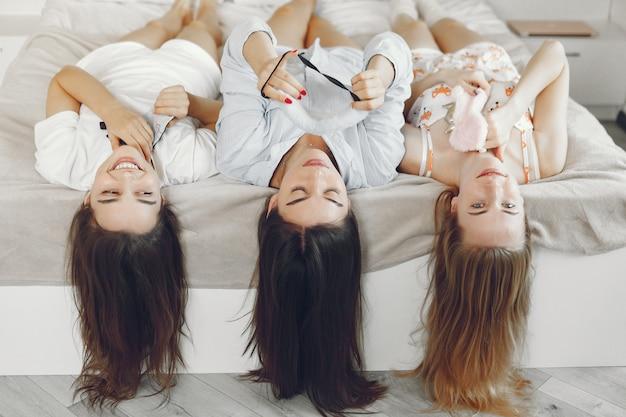 Trzy dziewczyny bawią się w domu w piżamie