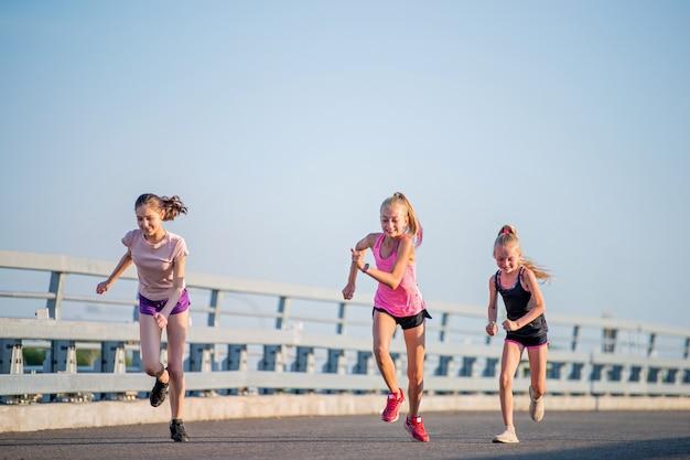 Trzy dziewczyny biegają w słoneczny letni wieczór