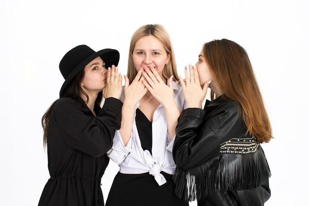 Trzy dziewczyny dyskutują ze sobą. zdjęcie na białym tle