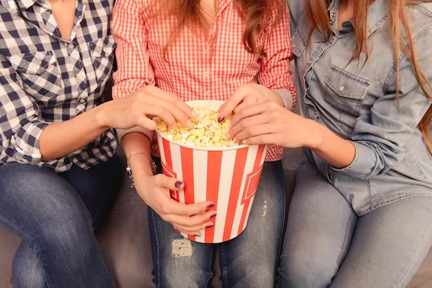 Trzy dziewczyny jedzące popcorn w domu