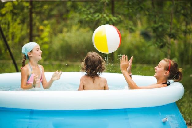 Trzy dziewczyny pływają w niebieskim basenie i bawią się piłką