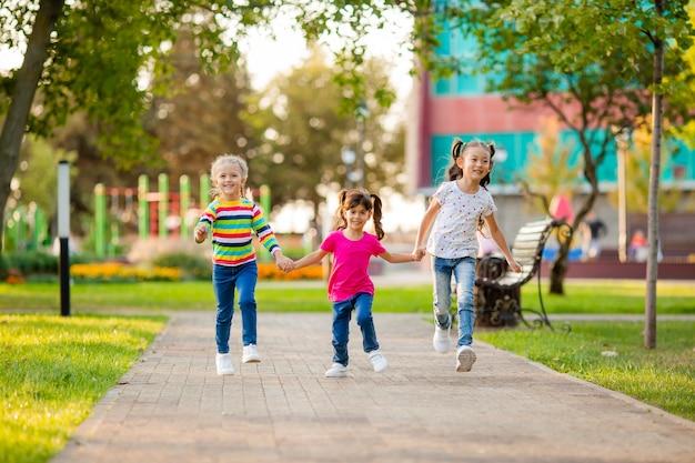 Trzy dziewczyny pochodzenia azjatyckiego, europejskiego i indyjskiego biegają latem w parku
