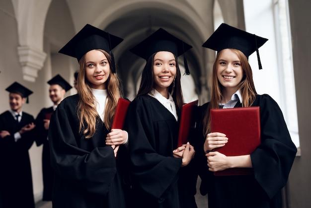Trzy dziewczyny pozują do kamery na uniwersytecie.