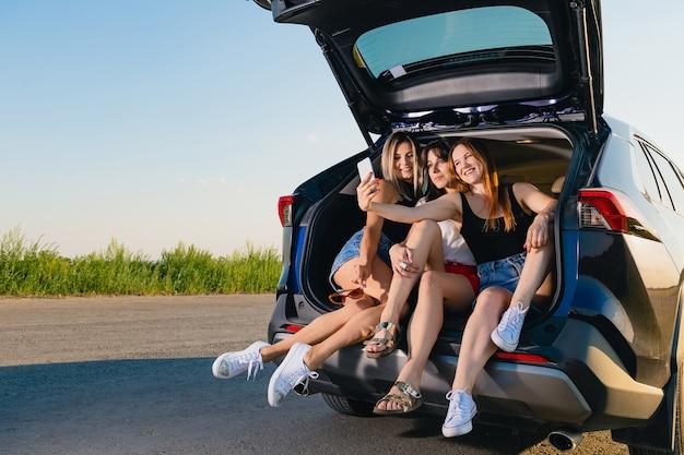 Trzy dziewczyny robią sobie razem selfie. blondynka, brunetka i rudowłose młode kobiety usiąść i zrelaksować się z tyłu pojazdu, rozmawiając podczas podróży przygodowej w przyrodzie.