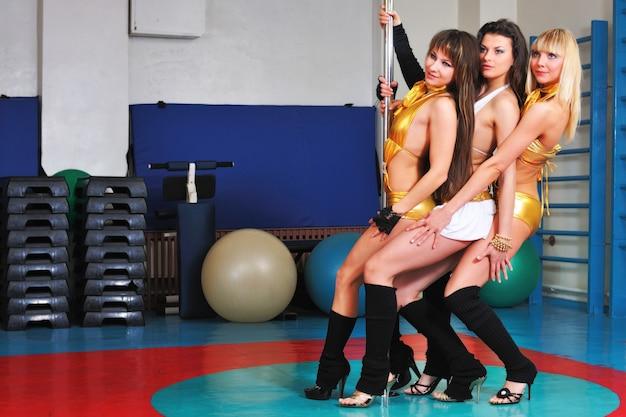 Trzy dziewczyny tancerki w jasnych strojach tanecznych pozowanie w pobliżu bieguna. sala taneczna z przedmiotami do uprawiania sportu