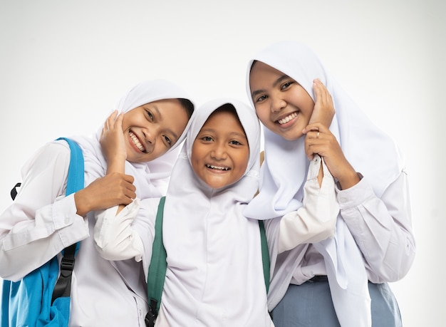 Trzy dziewczyny w chustach na głowach w szkolnych mundurkach stoją uśmiechnięte i czule gestykulują ...