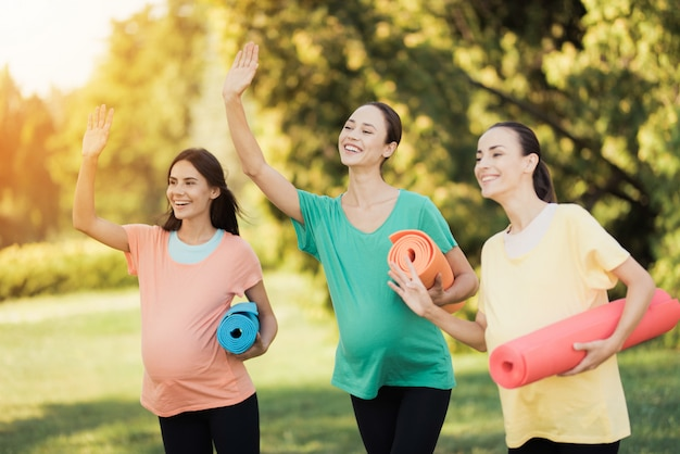 Trzy dziewczyny w ciąży stwarzających w parku z matami do jogi