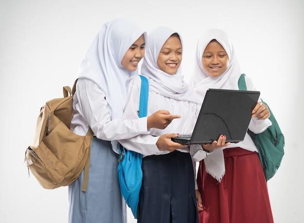 Trzy dziewczyny w welonach w szkolnych mundurkach stoją razem uśmiechając się przy laptopie i niosą plecaki