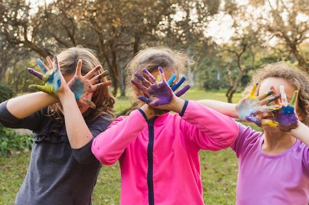 Trzy dziewczyny zakrywające twarze malowanymi palmami