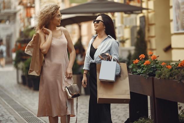 Trzy eleganckie kobiety z torby na zakupy w mieście