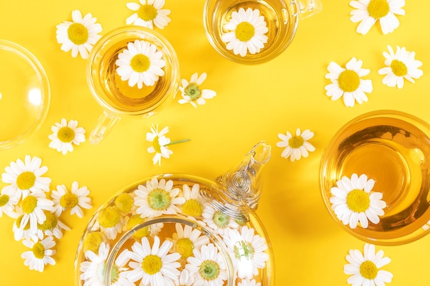 Trzy filiżanki herbaty i przezroczysty imbryk z kwiatami rumianku. rumiankowa herbata