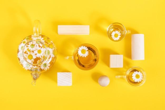 Trzy filiżanki herbaty rumiankowej, przezroczysty imbryk i drewno o geometrycznym kształcie