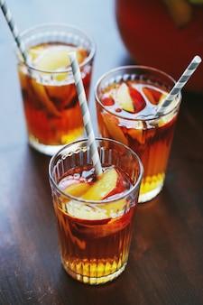 Trzy filiżanki żółtego soku brzoskwiniowego na drewnianym stole