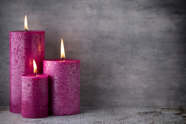 Trzy fioletowe świece na szarej powierzchni, dekoracja świąteczna.