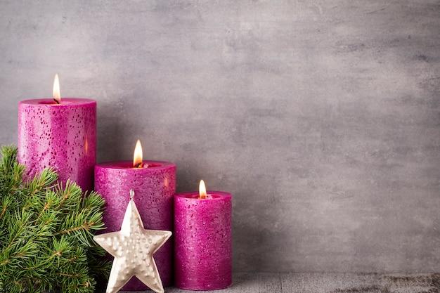 Trzy fioletowe świece na szarym tle, świąteczne dekoracje. nastrój adwentowy.