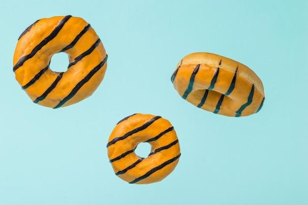 Trzy glazurowane pomarańczowe pączki latające na niebieskiej powierzchni