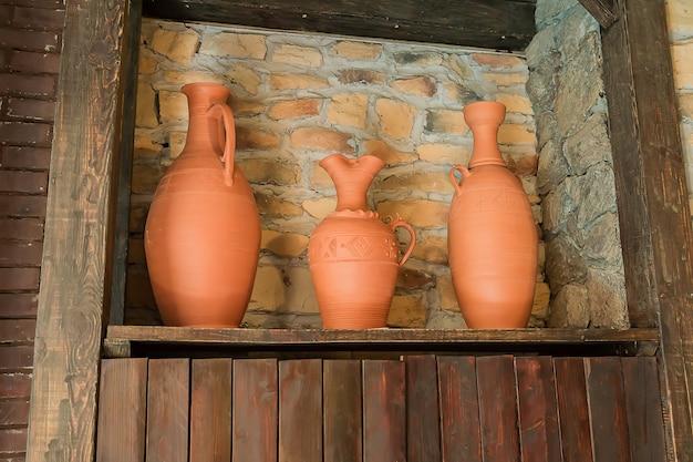 Trzy gliniane wazy na drewnianej półce. dekoracja wnętrz, styl orientalny