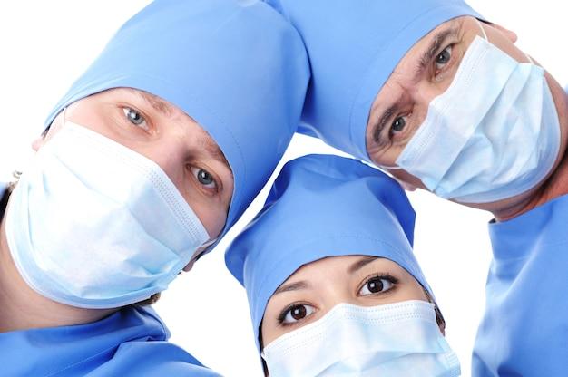 Trzy głowy chirurga z bliska na białym tle