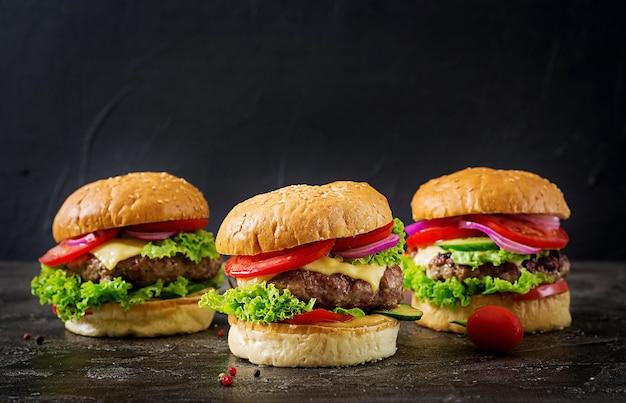 Trzy hamburger z wołowiny mięsnym hamburgerem i świeżymi warzywami na ciemnym tle.