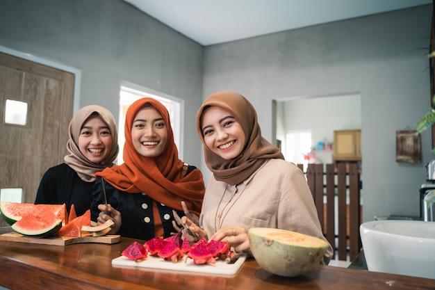 Trzy hidżab kobieta uśmiecha się, gdy przygotowuje plasterek owoców