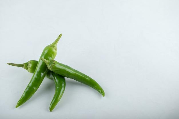 Trzy hit papryczki chili na białym tle.