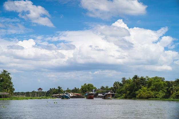 Trzy holowniki ciągną transportery piasku na środku rzeki w pogodny dzień.