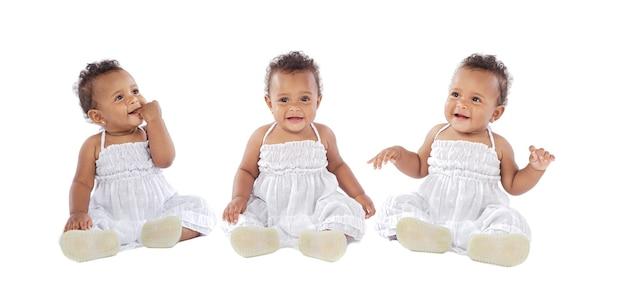 Trzy identyczne dzieci siedzące na podłodze na białym tle