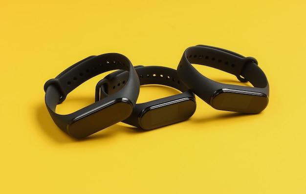 Trzy inteligentne bransoletki na żółtym tle