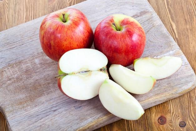 Trzy jabłka na drewnianej desce do krojenia