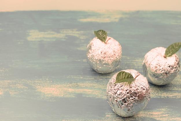 Trzy jabłka owinięte w folię to naturalne zielone liście.
