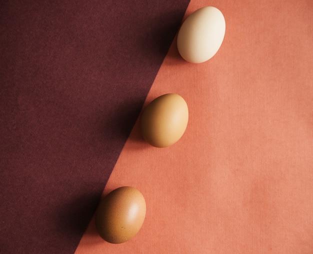 Trzy jaja kurze układane są na papierze o naturalnych kolorach. tekstura papieru i jajka jest beżowa. pisanki.