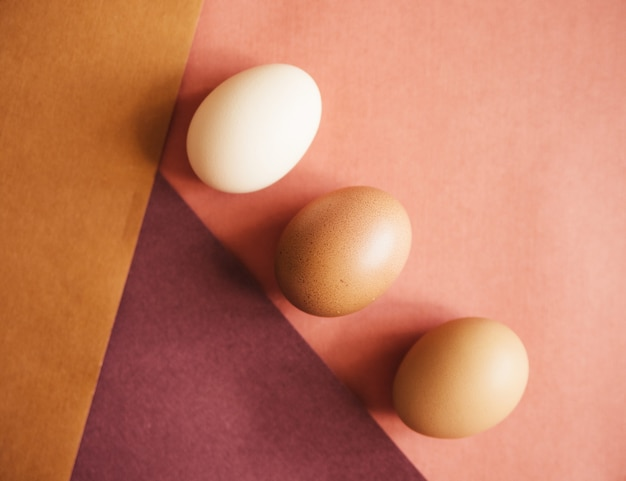 Trzy jaja kurze układane są na papierze o naturalnych kolorach. tekstura papieru i jajka jest beżowa.