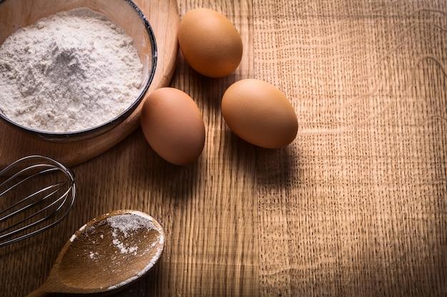 Trzy jajka mąki w misce pusta łyżka corolla na desce